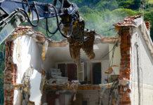 La demolizione di una abitazione colpita dal sisma in una frazione di Arquata del Tronto