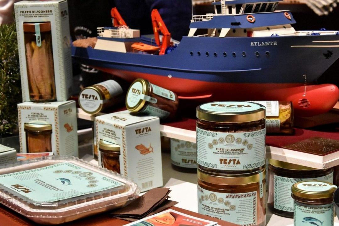 I prodotti di Testa Conserve, con il peschereccio Atlante sullo sfondo